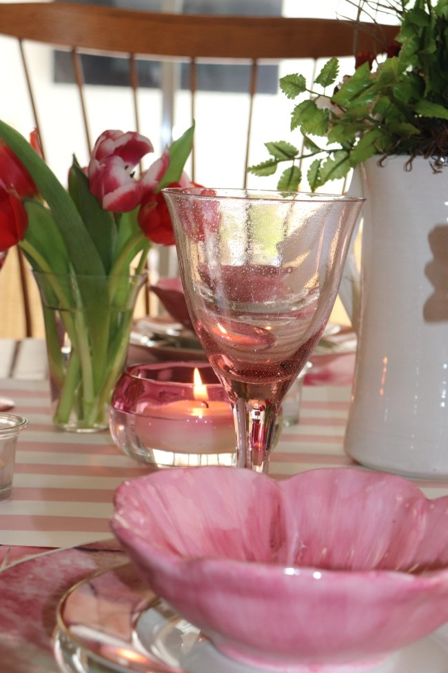 Pink dishes on table with flower bowl