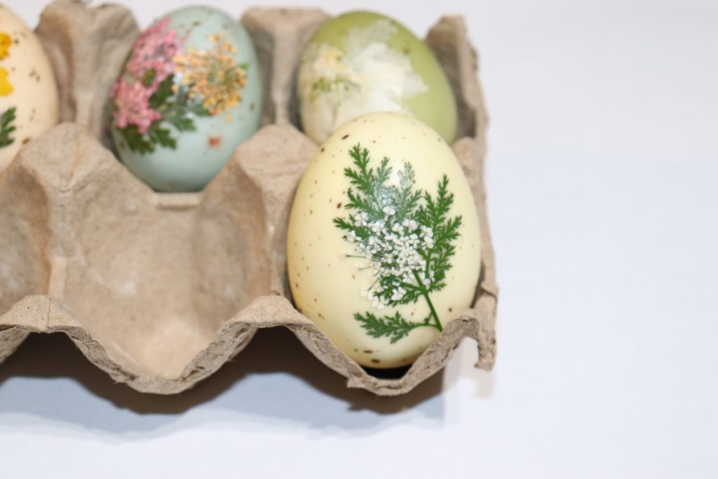 Faux egg with dried flower applied to surface