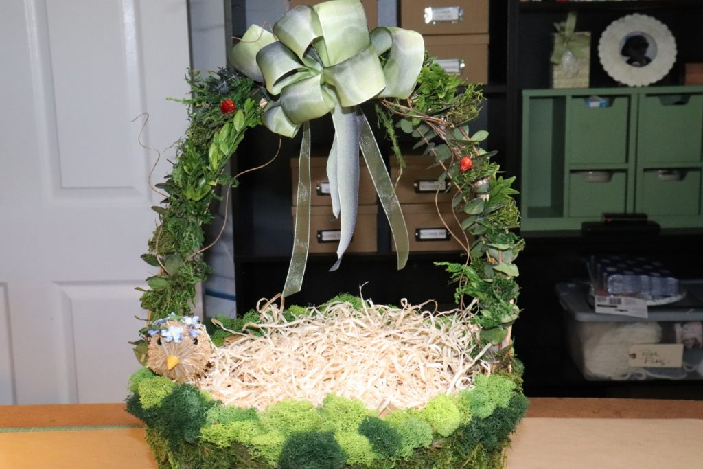 Basket with green grass and bow