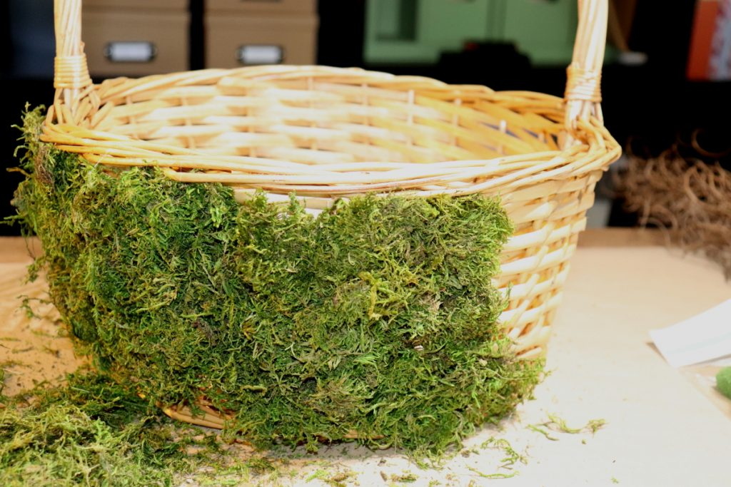wicker basket with moss glued onto the basket