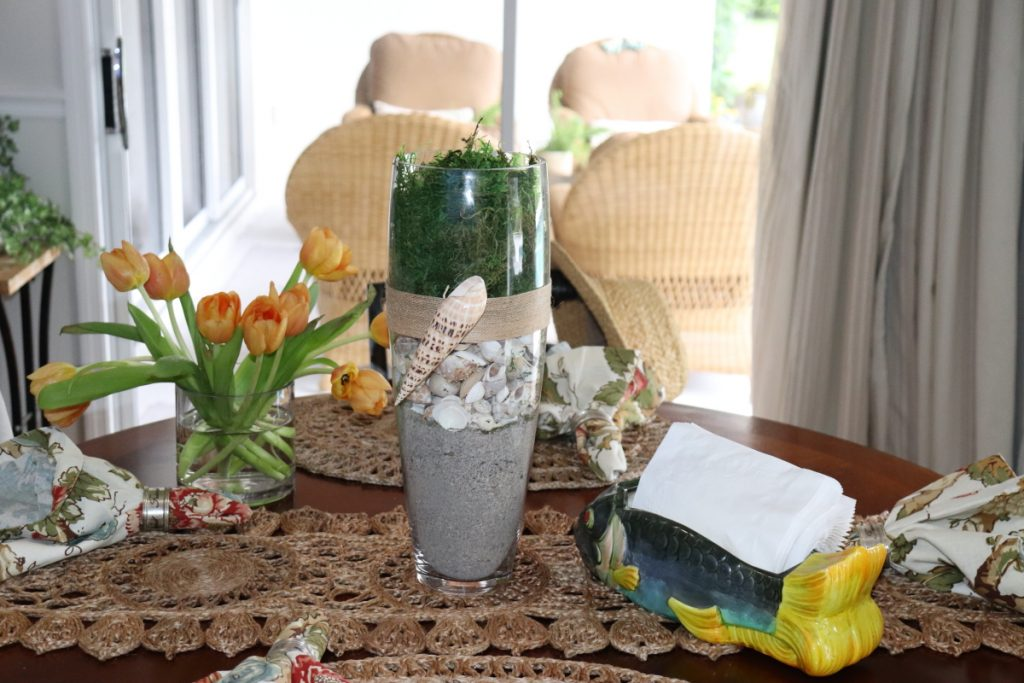 Vase filled with sand, shells and grass
