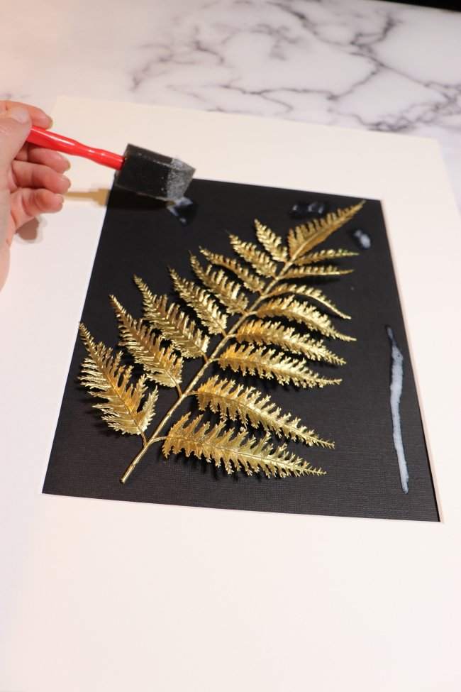 picture of hand placing adhesive for the gold leaf
