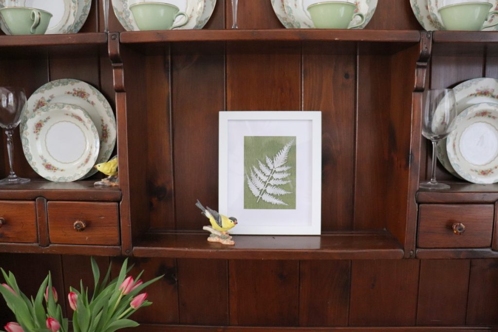 white frame with white fern placed in brown hutch