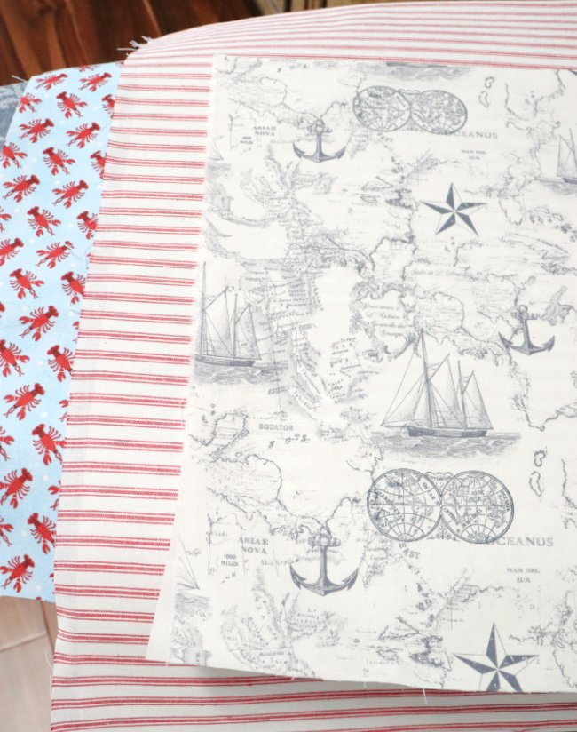 three different fabrics, one blue with red lobsters, red stripe on white canvas and blue nautical navigational