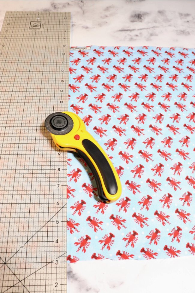 light blue fabric with red lobsters and a ruler and fabric roller cutter