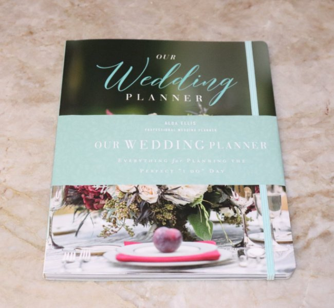 A wedding planner book. It is closed with a floral arrangement on the front cover.