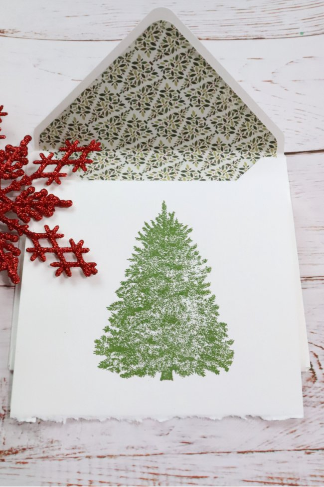 This decorative notecard is for the ocassion Christmas. It is a white envelope with christmas trees for insert and the card is white with a large christas tree on it.