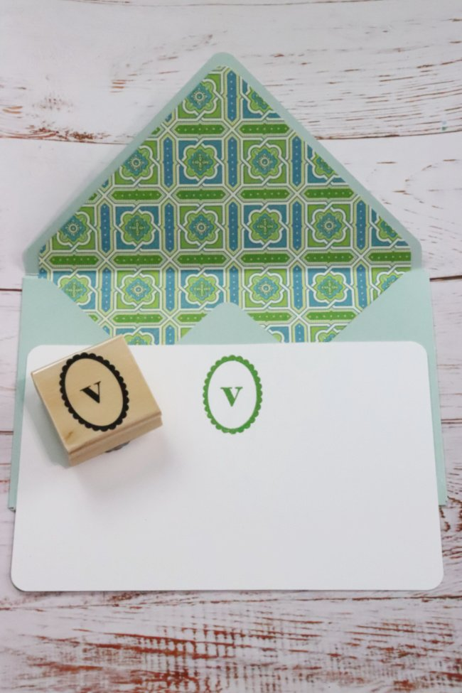 This decorative DIY note card has a pale green envelope with a blue and green geoetrical pattern. The card is white with an embossed letter V in the middle upper card