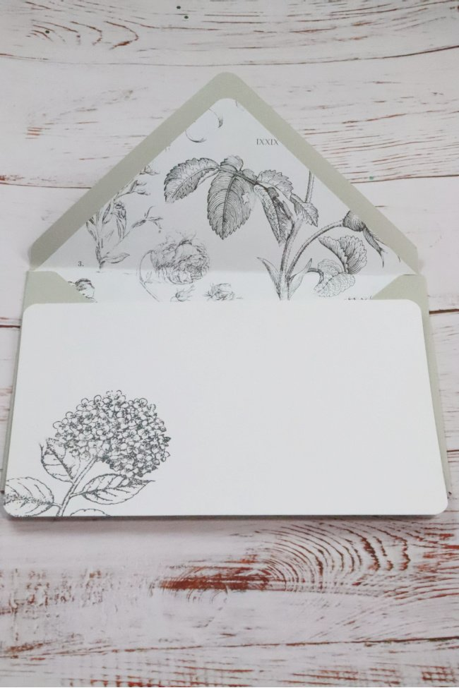 This decorative note card is a taupe color envelope and a black and white botanical print. the card is white with an embossed hydranga on the left corner.
