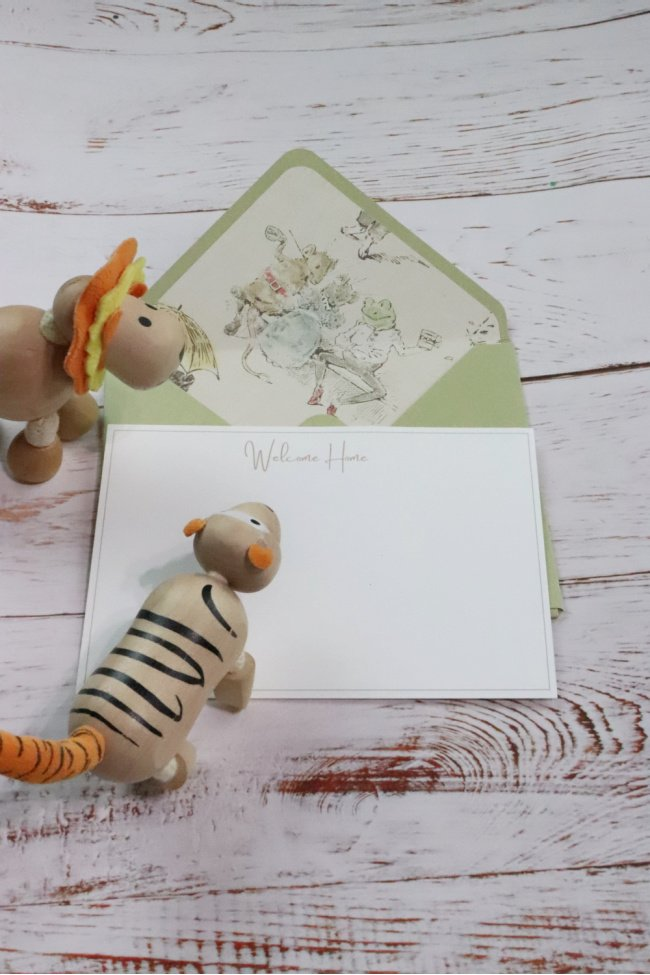 This decorative DIY note card has a green background and the insert is nursery style mouse and frogs in pale colors. The card is white with the words welcome home written in the middle top Welcome HOme