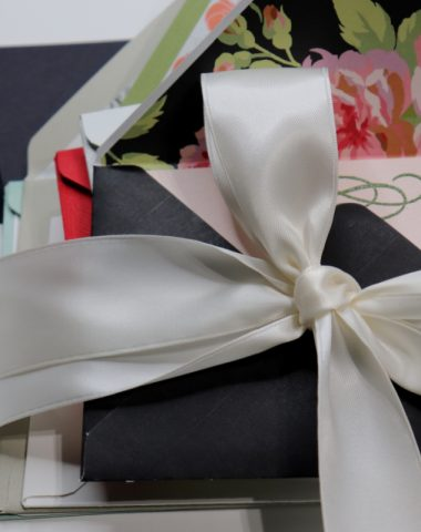 A stack of note cards tied together with a cream satin ribbon. Te first envelope is black with a pink card inside and a floral motif as a decorative liner.