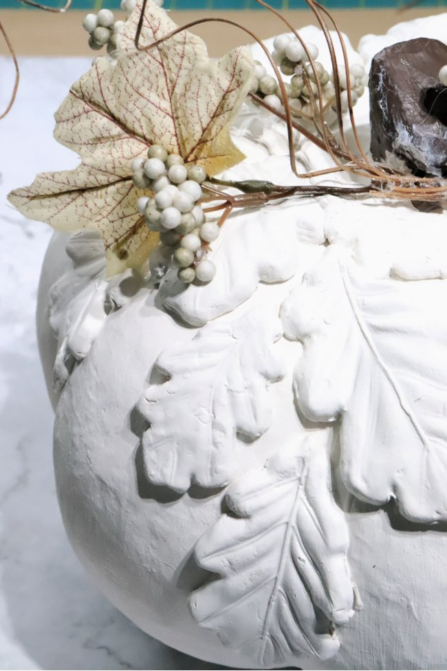 The final touches of adding florals to an air dry clay fall tutorial a white pumpkin.