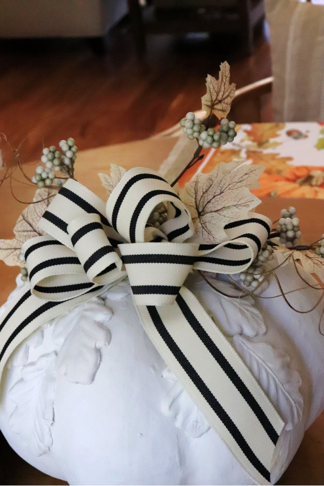 A finished tutorial of a white pumpkin with white clay leaves and decorated with ribbon and flora
