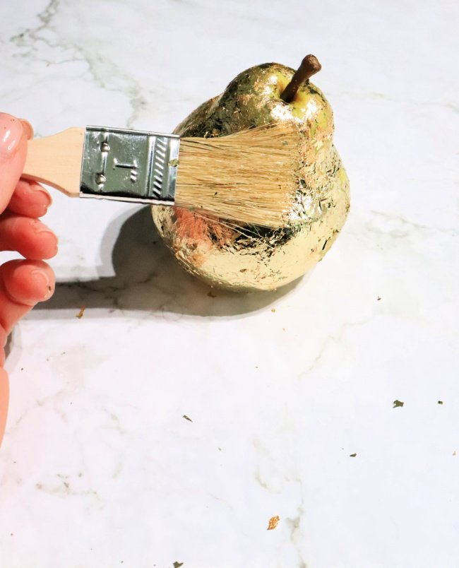 Demonstrates brushing the pear with paintbrush to burnish the gold foil