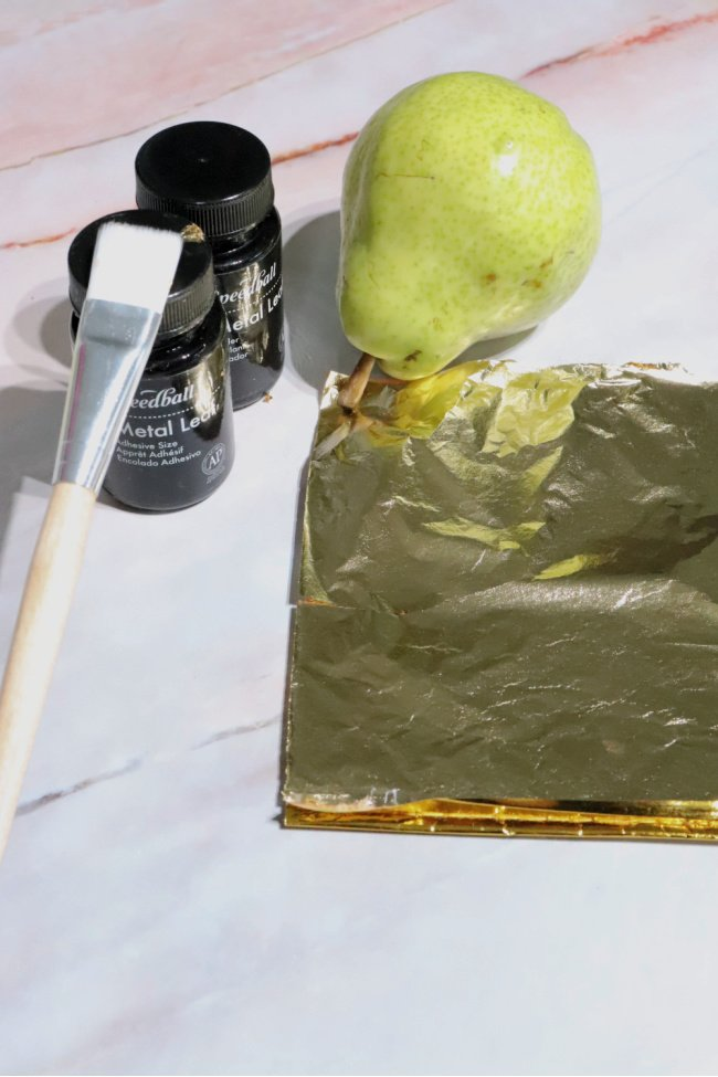 This is a photo of gathering supplies for gold leafing a pear