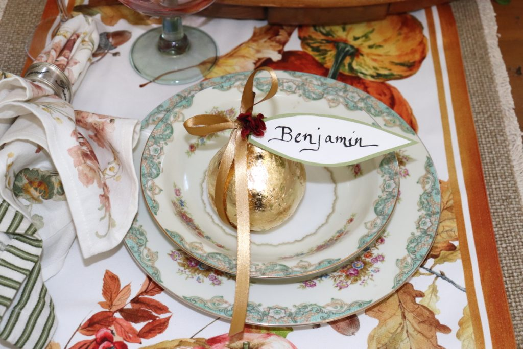 The image shows a pear sitting in the middle of a table setting with a name printed on an attached paper lear. The pear has gold leaf applied to it. It is demonstrating how it can be used as a placecard.